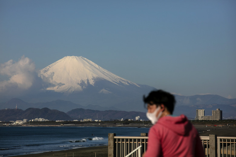 FILE – In this Feb. 27, 2020, file photo, a man wearing a mask visits a beach as snow-capped Mount Fuji is visible in the distance in Fujisawa, Japan. The tentacles of cancelling the Tokyo Olympics — or postponing or staging it in empty venues — would reach into every corner of the globe, much like the spreading virus that now imperils the opening ceremony on July 24. (AP Photo/Jae C. Hong, File)