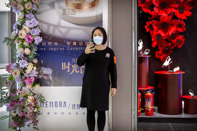 A clerk wears a face mask as she stands outside a store at a mostly empty shopping mall in Beijing, Saturday, March 7, 2020. Crossing more borders, the new coronavirus hit a milestone, infecting more than 100,000 people worldwide as it wove itself deeper into the daily lives of millions, infecting the powerful, the unprotected poor and vast masses in between. (AP Photo/Mark Schiefelbein)