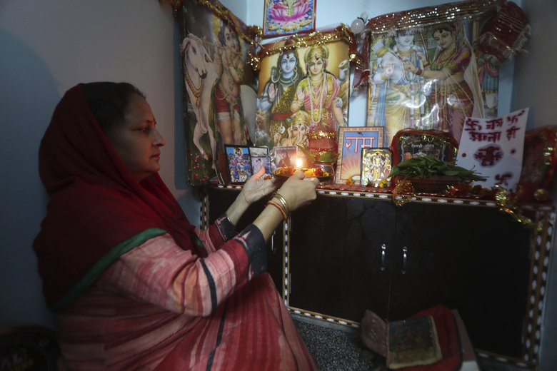 A Hindu woman prays inside their house on the first day of Navratri festival in Jammu, India, Wednesday, March 25, 2020. The world's largest democracy went under the world's biggest lockdown Wednesday, with India's 1.3 billion people ordered to stay home in a bid to stop the coronavirus pandemic from spreading and overwhelming its fragile health care system as it has done elsewhere. For most people, the new coronavirus causes mild or moderate symptoms, such as fever and cough that clear up in two to three weeks. For some, especially older adults and people with existing health problems, it can cause more severe illness, including pneumonia and death. (AP Photo/Channi Anand)