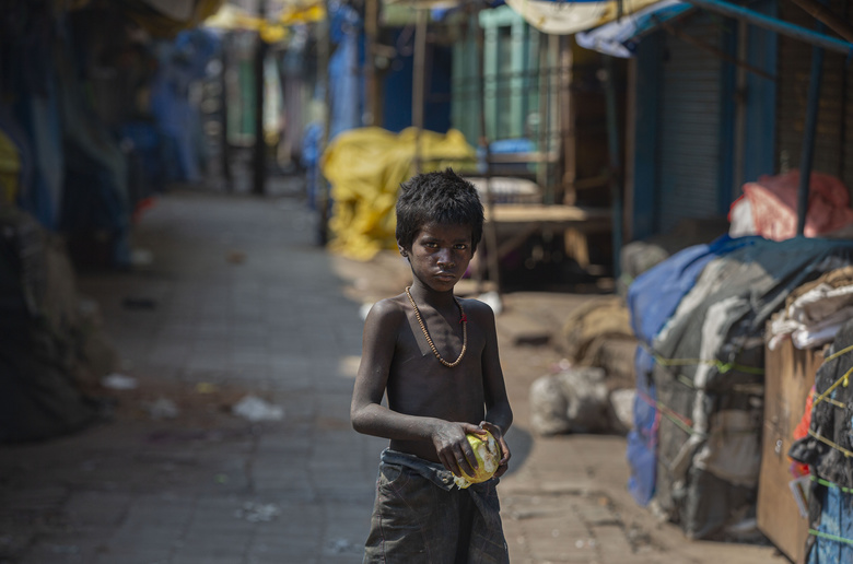 A homeless boy collects rotten fruits from a deserted fruit market during lockdown in Gauhati, India, Wednesday, March 25, 2020. The world's largest democracy went under the world's biggest lockdown Wednesday, with India's 1.3 billion people ordered to stay home in a bid to stop the coronavirus pandemic from spreading and overwhelming its fragile health care system as it has done elsewhere. For most people, the new coronavirus causes mild or moderate symptoms, such as fever and cough that clear up in two to three weeks. For some, especially older adults and people with existing health problems, it can cause more severe illness, including pneumonia and death. (AP Photo/Anupam Nath)