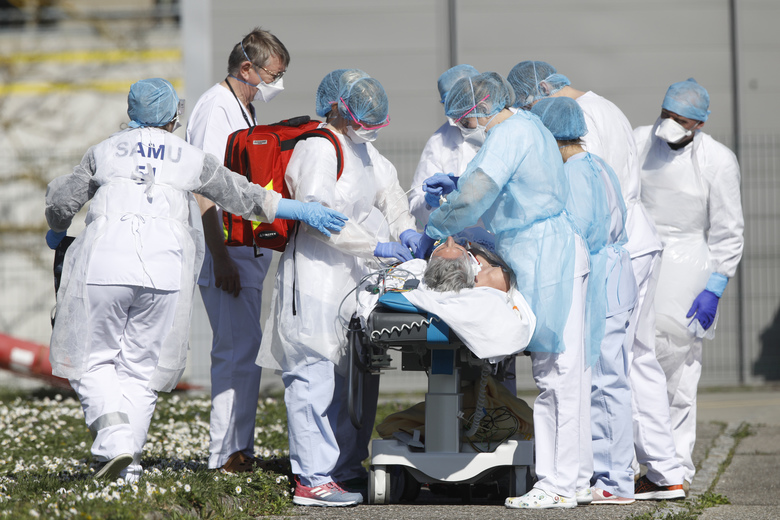 FILE – In this photo taken Monday March 23, 2020, a victim of the Covid-19 virus is evacuated from the Mulhouse civil hospital, eastern France. The Grand Est region is now the epicenter of the outbreak in France, which has buried the third most virus victims in Europe, after Italy and Spain. For most people, the new coronavirus causes only mild or moderate symptoms. For some it can cause more severe illness. (AP Photo/Jean-Francois Badias, File)