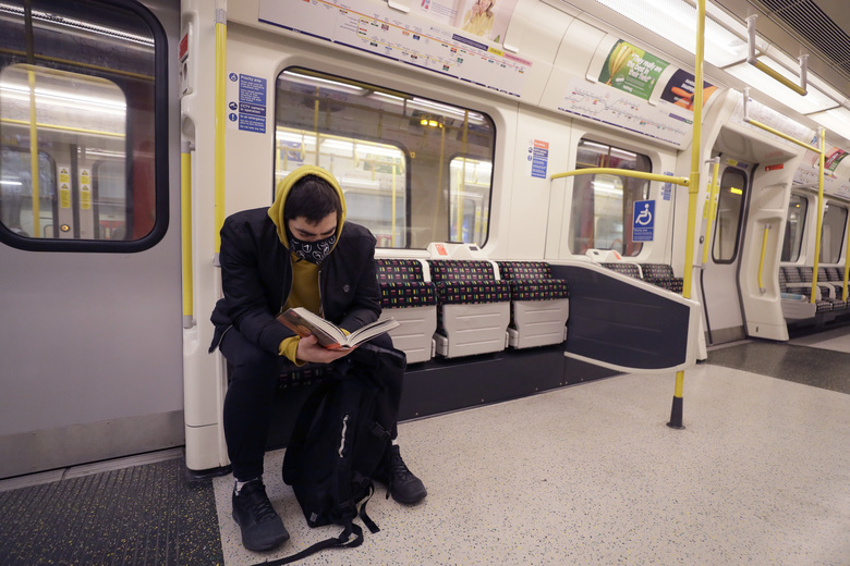A man wears a mask as he reads on a tube in London, Monday, March 16, 2020. For most people, the new coronavirus causes only mild or moderate symptoms, such as fever and cough. For some, especially older adults and people with existing health problems, it can cause more severe illness, including pneumonia. (AP Photo/Kirsty Wigglesworth)