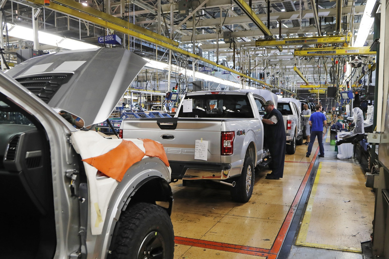 Auto workers work on Ford F-150 trucks at an assembly plant in Dearborn, Michigan, in 2018. Ford and other automakers are shutting down temporarily because of the coronavirus. (Carlos Osorio / The Associated Press, file)