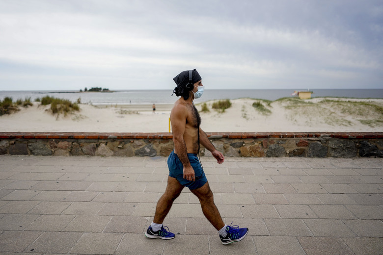 FILE – In this March 17, 2020 file photo, a man gets some exercise along the seaside in Montevideo, Uruguay. Many countries in Latin American and the Caribbean saw their first cases of novel coronavirus arrive with jetsetting members of the elite returning from vacations or work trips to Europe and the United States. (AP Photo/Matilde Campodonico, File)