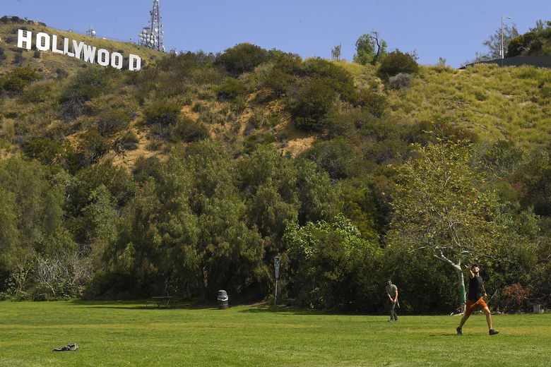 Two men play catch at Lake Hollywood Park near the famed Hollywood Sign, Saturday, March 28, 2020, in Los Angeles. With cases of coronavirus surging and the death toll surpassing 100, lawmakers are pleading with cooped-up Californians to spend a second weekend at home to slow the spread of the infections. It has been more than a week since Gov. Gavin Newsom barred 40 million residents from going outdoors except for essentials. Even so, reports of crowds have prompted local and state officials to warn that ignoring social distancing, park and beach closures could spread the virus, which already is surging. (AP Photo/Mark J. Terrill)