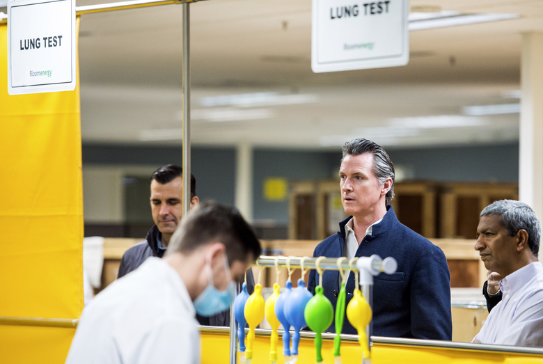 California Gov. Gavin Newsom, second from right, is given a tour of the Bloom Energy Sunnyvale, Calif., campus Saturday, March 28, 2020. Bloom Energy is a fuel cell generator company that has switched over to refurbishing ventilators as an increasing number of patients experience respiratory issues as a result of COVID-19. (Beth LaBerge/KQED via AP, Pool)