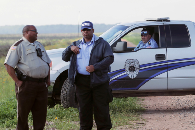 Security personnel for Formosa block a road leading to a burial ground as members of RISE St. James seek access to the site, on Formosa property, in St. James Parish, La., Wednesday, March 11, 2020. They then allowed access after talking to a St. James Sheriffs deputy, left. Archaeologists have found that the land bought for a planned $9.4 billion plastics complex may include up to seven slave cemeteries rather than two previously described, local activists said Wednesday. (AP Photo/Gerald Herbert)