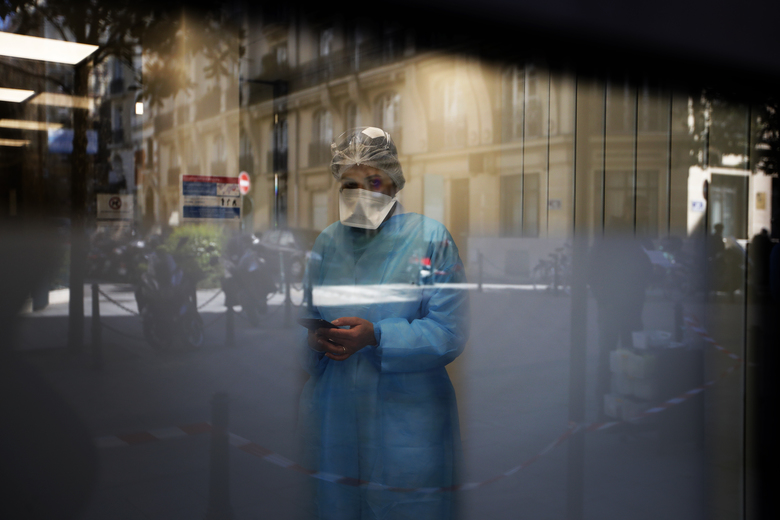 Biologist doctor Caroline Gutsmuth gives a phone call in medical biology laboratory who opened a coronavirus drive-thru testing site, in Neuilly-sur-Seine, near Paris, Monday, March 23, 2020. French President Emmanuel Macron urged employees to keep working in supermarkets, production sites and other businesses that need to keep running amid stringent restrictions of movement due to the rapid spreading of the new coronavirus in the country. For most people, the new coronavirus causes only mild or moderate symptoms. For some it can cause more severe illness, especially in older adults and people with existing health problems. (AP Photo/Christophe Ena)