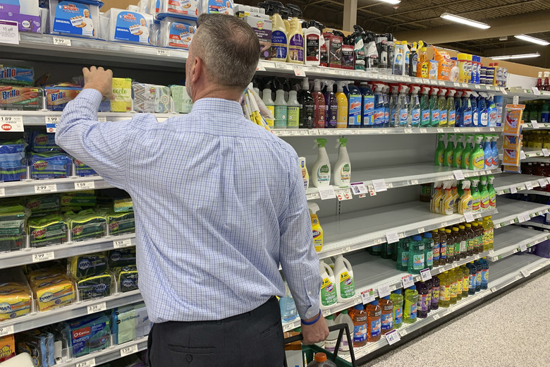 A customer looks for scrubbing pads near empty shelves of cleaning supplies at a Publix Supermarket amid concern over the COVID-19 virus on Monday, March 9, 2020, in Pembroke Pines, Fla. (AP Photo/Brynn Anderson)