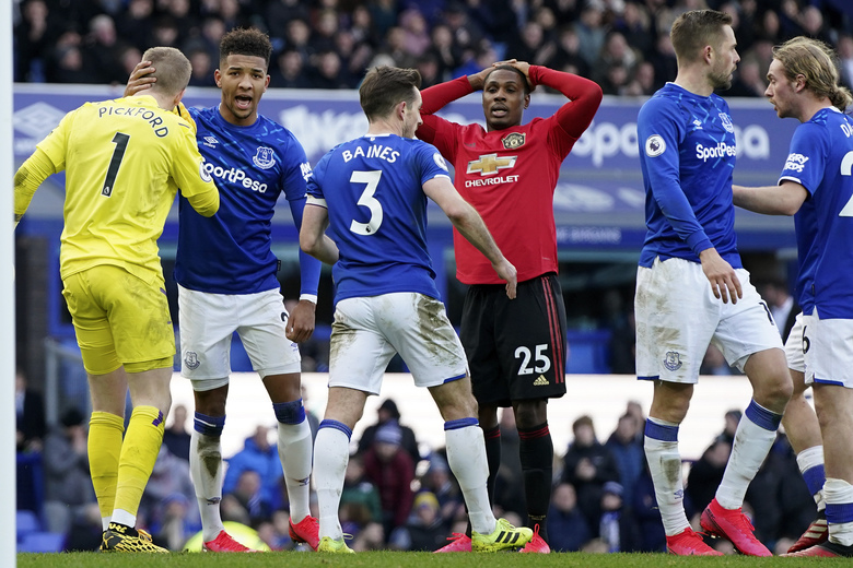 Manchester United's Odion Ighalo, center, reacts after having a shot at goal stopped by Everton's goalkeeper Jordan Pickford, left, during the English Premier League soccer match between Everton and Manchester United at Goodison Park in Liverpool, England, Sunday, March 1, 2020. (AP Photo/Jon Super)