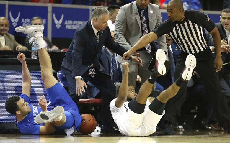 Air Force's Sid Tomes, left, and San Diego State's KJ Feagin slide off the court chasing a loose ball during the first half of a Mountain West Conference tournament NCAA college basketball game Thursday, March 5, 2020, in Las Vegas. (AP Photo/Isaac Brekken)