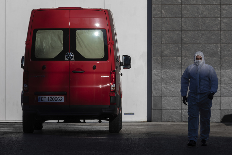 A spanish UME (Emergency Army Unit) soldier walks out of Madrid's ice rink turned into a temporary morgue due the COVID-19 crisis in Madrid, Spain, Monday, March 23, 2020. As cases in China ebbed, the dangers to Europe and the U.S. have grown exponentially, although Germany on Monday cautiously reported some flattening of its infection curve. More than 1.5 billion around the world have been told to stay in their homes. For most people, the new coronavirus causes only mild or moderate symptoms. For some it can cause a more serious illness. (AP Photo/Bernat Armangue)