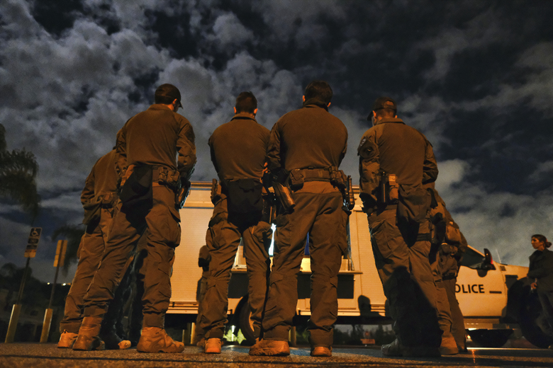 A DEA agents are briefed in a parking lot prior to an arrest of a suspected drug trafficker on Wednesday, March 11, 2020 in Diamond Bar, Calif. In early-morning raids Wednesday, federal agents fanned out across the U.S., culminating a six-month investigation with the primary goal of dismantling the upper echelon of the Jalisco New Generation Cartel, known as CJNG. (AP Photo/Richard Vogel)