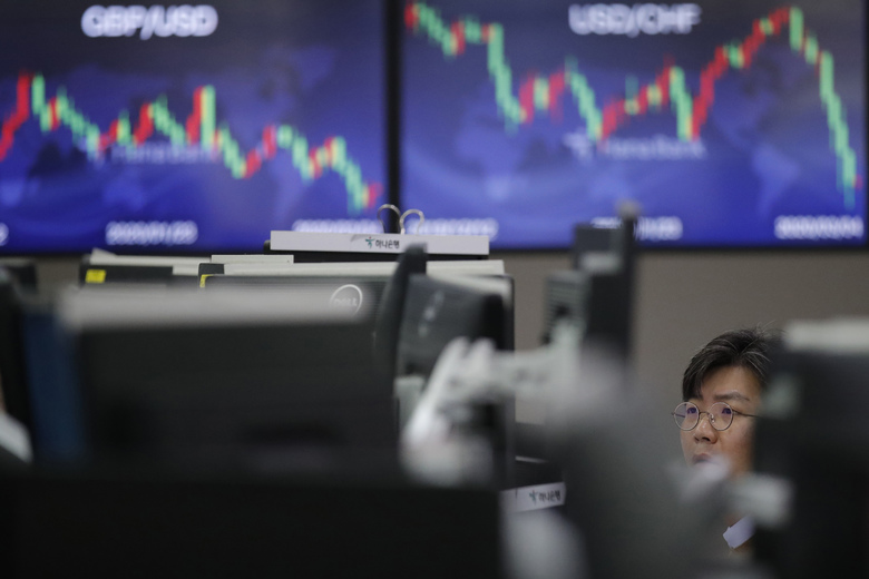 A currency trader watches computer monitors at the foreign exchange dealing room in Seoul, South Korea, Wednesday, March 4, 2020. Asian stock markets were mostly higher Wednesday after Wall Street sank despite an emergency U.S. interest cut aimed at defusing fears a virus outbreak might depress global economic activity. (AP Photo/Lee Jin-man)