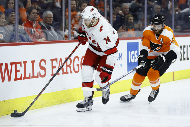 Carolina Hurricanes' Jaccob Slavin, left, tries to keep away from Philadelphia Flyers' Sean Couturier during the second period of an NHL hockey game, Thursday, March 5, 2020, in Philadelphia. (AP Photo/Matt Slocum)