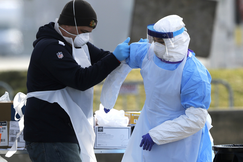 In this March 25, 2020 photo, medical personnel help each other at a federal COVID-19 drive-thru testing site in the parking lot of Walmart in North Lake, Ill. (AP Photo/Nam Y. Huh)