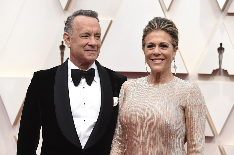 """FILE – In this Feb. 9, 2020 file photo, Tom Hanks, left, and Rita Wilson arrive at the Oscars at the Dolby Theatre in Los Angeles. The couple have tested positive for the coronavirus, the actor said in a statement Wednesday, March 11. The 63-year-old actor said they will be """"tested, observed and isolated for as long as public health and safety requires."""" (Photo by Jordan Strauss/Invision/AP, File)"""