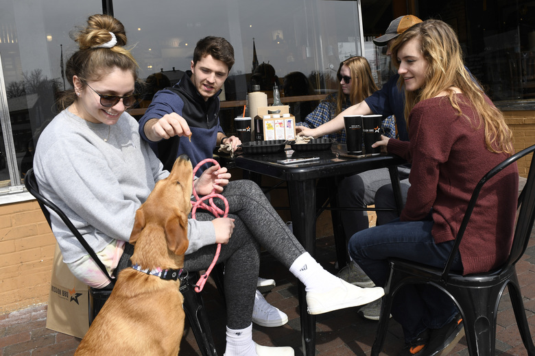 Clay Colehouse of Crownsville, Md., second from left, gives the dog Marty a treat as he and his friends, from left, Erin Carroll of Severna Park, Md., Jessica Goblin of Severna Park, Md., Travis Victorio of Millersville, Md., and Mary Fitzell of Millersville, Md., have lunch during a visit to Annapolis, Monday, March 16, 2020. Maryland Gov. Larry Hogan ordered the closure of bars, restaurants, gyms and movie theaters across the state in response to coronavirus beginning at 5 p.m. Monday. Drive-thru, carryout and delivery service will still be allowed. The friends gathered for lunch because they are home from college. (AP Photo/Susan Walsh)