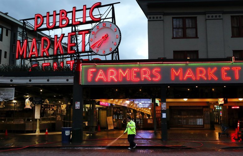 At dusk a worker cleans the sidewalk ways under the Pike Place Market clock.   What's open can be found on the market's blog: pikeplacemarket.org   LO Pike Place Market, largely shutdown but a number of stalls still serving the public. (Photo essay multiple days)  Wednesday April 3, 2020 213490