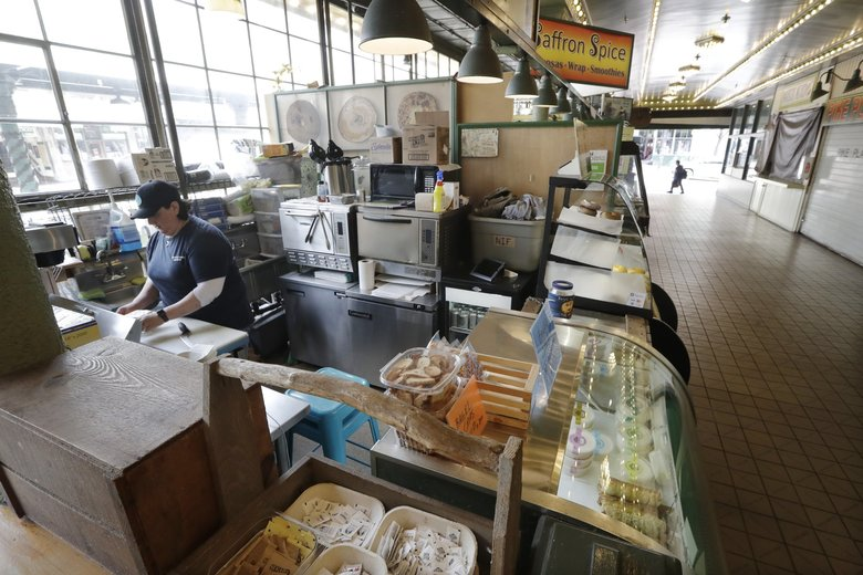 Samantha Maddocks at a bagel shop last Thurday, the lone shop open in a walkway in Seattle's Pike Place Market. More than one in 10 workers have lost their jobs in just the past three weeks to the coronavirus outbreak. (Elaine Thompson / The Associated Press)