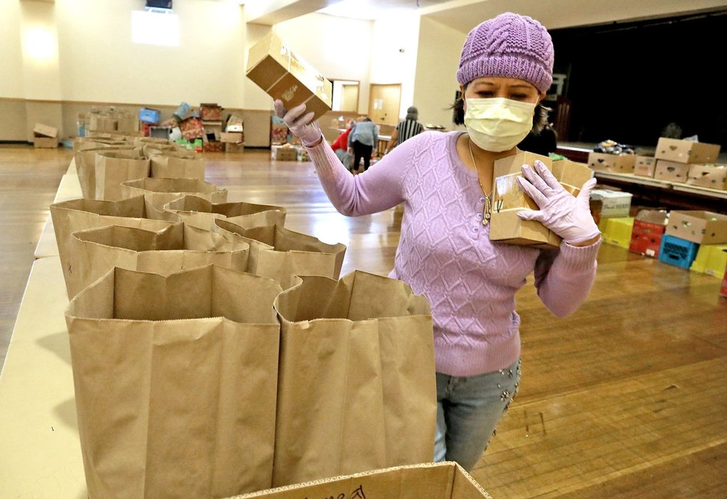 At the Filipino Community Center of Seattle, Lolita Lawson adds food items to be delivered to seniors stuck at home during the coronavirus. (Greg Gilbert / The Seattle Times)