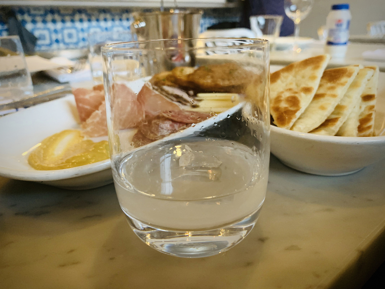 A glass of ouzo sparkles with the meze platter and pita at Omega Ouzeri on Capitol Hill. (Tantri Wija)