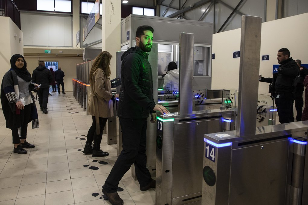 Khaled Habyeab, 30, as uses his biometric permit to prompt an automatic gate to open as he crosses the Qalandiya checkpoint in northern Jerusalem on February 25, 2020. Israel upgraded its West Bank checkpoints with facial recognition technology to verify Palestinians' identities as they cross into Israel. The new system is helping to shorten the amount of time it takes to cross the checkpoints, but the use of the technology is drawing criticism about the role the controversial technology plays in Israel's military control over Palestinians. (Heidi Levine / for The Seattle Times)