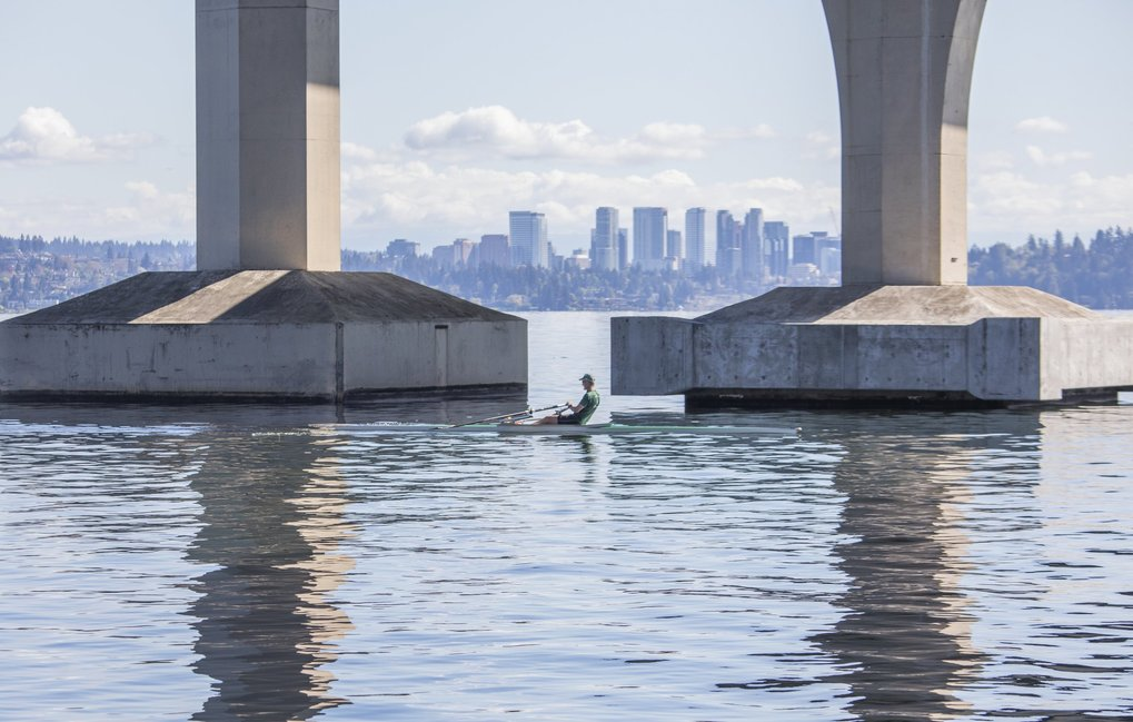 A rower crosses under the Interstate 90 bridge on Lake Washington.  Bellevue can be seen in the background. (Steve Ringman / The Seattle Times)