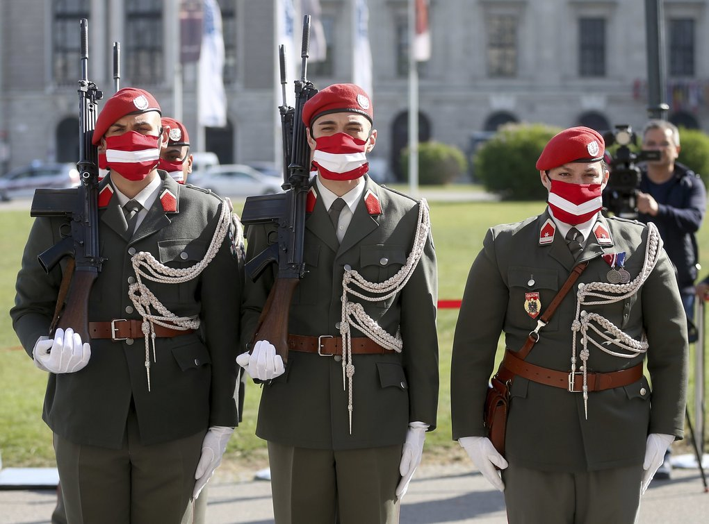 Soldiers' masks in Vienna show the Austrian national flag during a military ceremony to mark Monday's 75th anniversary of the re-establishment of the Republic of Austria. (Ronald Zak / The Associated Press)
