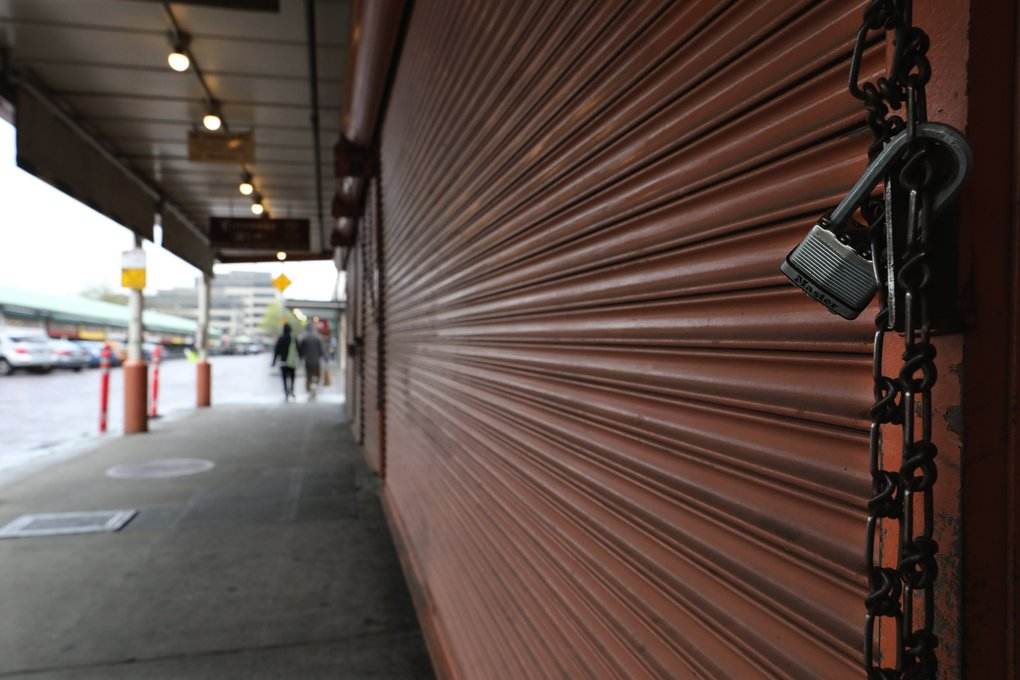 The descending metal curtain in front of Sotto Voce in Pike Place Market is padlocked. Adjacent businesses in this block have identical secure metal curtain closures. (Alan Berner / The Seattle Times)