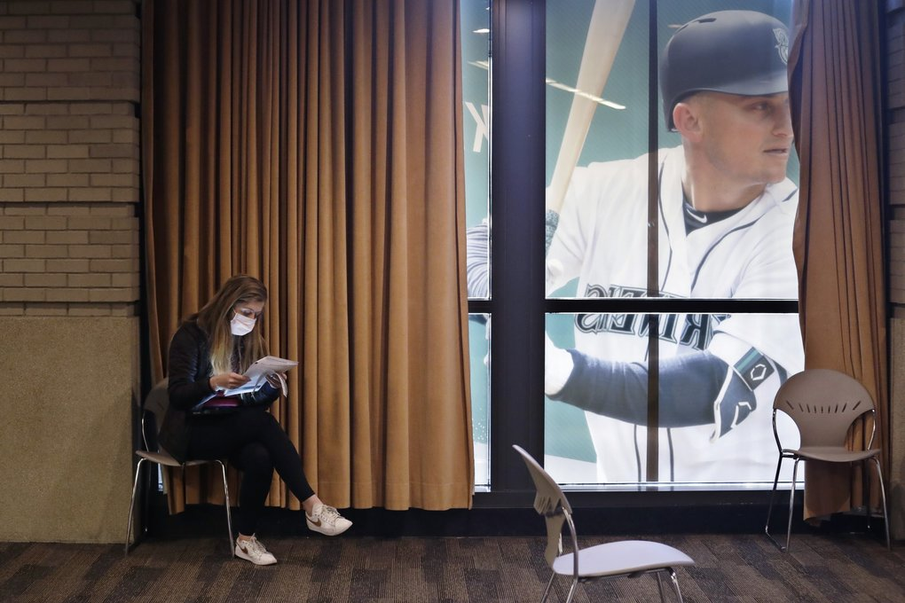 A blood donor fills out paperwork next to a window filled with an image of Mariners third baseman Kyle Seager at a pop-up donor event at T-Mobile Park on Monday. (Elaine Thompson / The Associated Press)