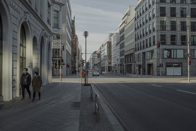People stroll the nearly empty streets of Berlin on Tuesday during the coronavirus pandemic. The German government on Wednesday issued a bleak assessment of the effects of the coronavirus, saying that the economy was headed for a steep recession and a surge in joblessness. (Emile Ducke / The New York Times)