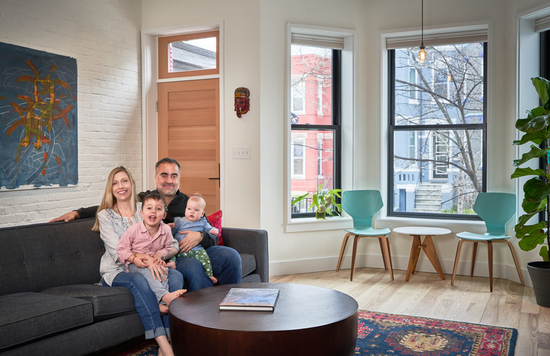 Amy and Jay Hariani with children Ashwin, 3, and Priya, 9 months, in the living room of their Washington, D.C., townhouse. (Photo for The Washington Post by Jeff Wolfram)
