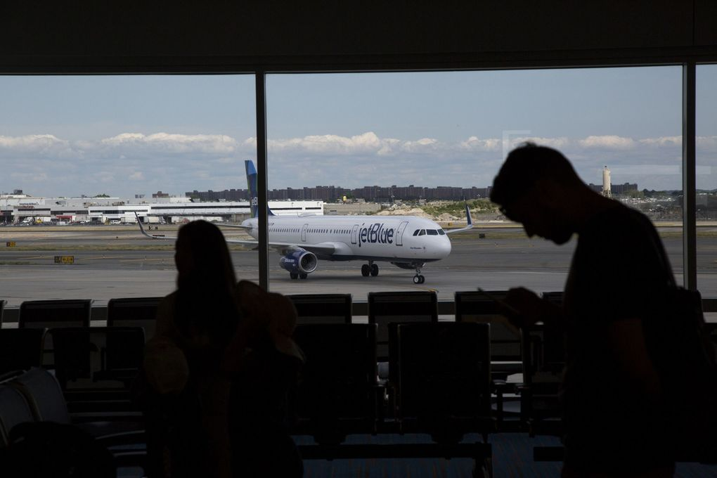 A JetBlue Airways Corp. plane taxis as passengers wait at John F. Kennedy International Airport in New York. (Michael Nagle / Bloomberg, file)
