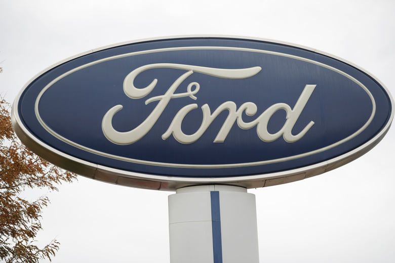 CORRECTS TO 15% TO $34.3 BILLION NOT NEARLY 16% TO $31.3 BILLION FILE – In this Oct. 20, 2019, file photo, the company logo stands over a long row of unsold vehicles at a Ford dealership in Littleton, Colo. Ford Motor Co. posted a $2 billion first-quarter net loss, blaming nearly all of it on the negative effects of the coronavirus. The automaker said Tuesday, April 28, 2020 that its revenue from January through March fell nearly 15% to $34.3 billion as most of its factories were shut down for the final week of the quarter. (AP Photo/David Zalubowski, File)