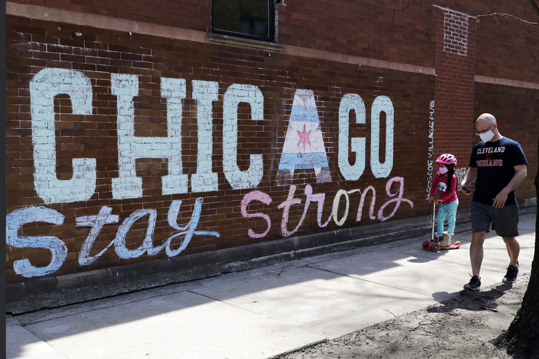 A man and child wearing protective masks pass an encouraging message 'Chicago Stay Strong,' chalked outside on a Roscoe Village neighborhood pub by artist Heather Gentile Collins, while people continue to contract COVID-19 in Chicago, Saturday, April 11, 2020. (AP Photo/Nam Y. Huh)