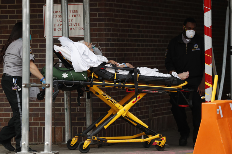 Emergency medical responders wheel an elderly patient into the emergency room at Brooklyn Hospital Center, Sunday, April 5, 2020, in New York. The hospital has been on the frontlines of the battle to treat high numbers of coronavirus patients during the viral pandemic. (AP Photo/Kathy Willens)