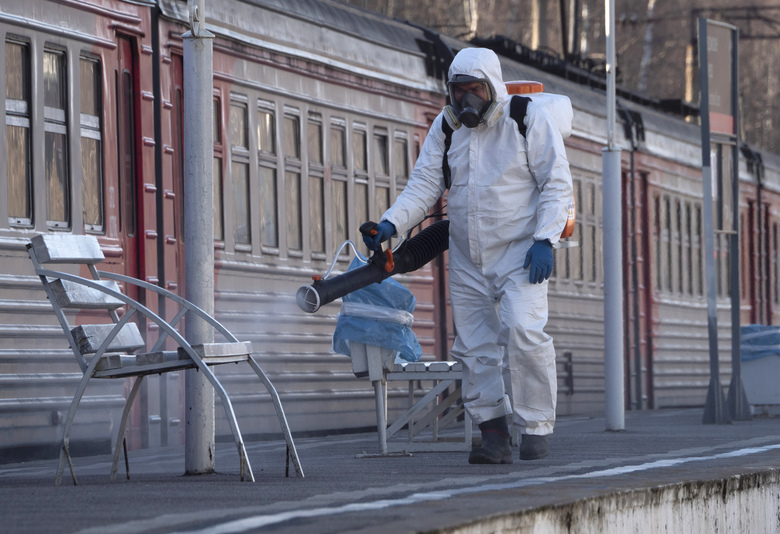 A member from a local veterinary service wearing protective suit sprays disinfectant on a platform of the railway station in Ladozhskoye Ozero village outside St. Petersburg, Russia, Saturday, April 4, 2020. The new coronavirus causes mild or moderate symptoms for most people, but for some, especially older adults and people with existing health problems, it can cause more severe illness or death. (AP Photo/Dmitri Lovetsky)