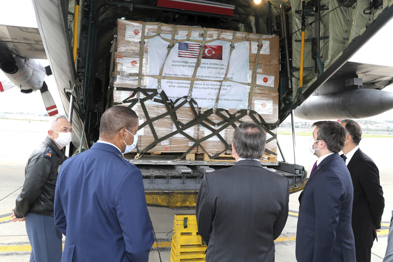 In this handout photo provided by the Turkish Defense Ministry, David M. Satterfield, the U. S. Ambassador to Turkey, center, watches as Turkish soldiers load a Turkish military cargo plane with Personal Protection Equipment donated by Turkey to help United States combat the new coronavirus outbreak, at the Etimesgut airport outside Ankara, Turkey, Thursday, April 30, 2020. Turkey is sending a second planeload of surgical masks, N95 masks and hazmat suits tor U.S. to help the country battle the coronavirus outbreak.(Turkish Defence Ministry via AP)