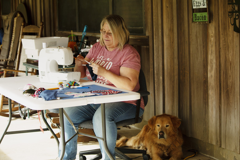 In this April 11, 2020, photo, Cathia Schmarje sews a face mask on the front porch of her home in Liberty County, Florida. She's sewn masks for her son and his employees, and she'll give some to townsfolk who need one. For weeks, there had been chatter across Liberty County in Florida's Panhandle about how the coronavirus could devastate the 8,300 people who live there. As the coronavirus spread across Florida, Liberty became the last county without a case. (AP Photo/Bobby Caina Calvan)