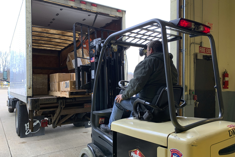In this March 20, 2020, photo, Terry Stratman, of the Missouri Department of Health and Senior Services, operates a forklift to load shipments of personal protective equipment onto a truck in Jefferson City, Mo. The items were being distributed to hospitals, emergency medical service agencies and other health care facilities across the state. (Caty Luebbert/Missouri State Emergency Management Agency via AP)