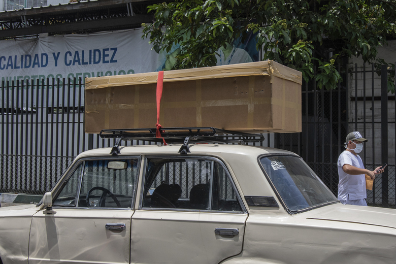 A cardboard coffin with a body sits on the roof rack of a car before it is taken away to be buried, outside the Teodoro Maldonado Hospital in Guayaquil, Ecuador, Monday, April 6, 2020. Guayaquil, a normally bustling city that has become a hot spot in Latin America as the coronavirus pandemic spreads, also has untold numbers dying of unrelated diseases that can't be treated because hospitals are overwhelmed. (AP Photo/Luis Perez)