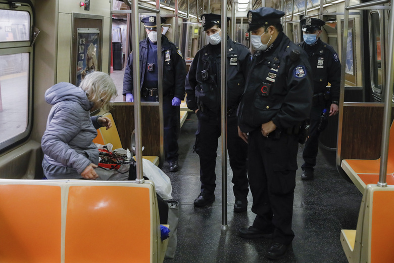 NYPD officers wake up sleeping passengers and direct them to the exits at the 207th Street A-train station, Thursday, April 30, 2020, in the Manhattan borough of New York. (AP Photo/John Minchillo)