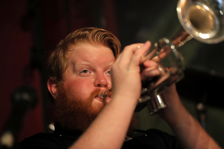 Doyle Cooper plays his trumpet has he performs a livestream gig with his mother, singer Leslie Cooper, and pianist Harry Mayronne, in an empty and closed Back Room at Buffa's in New Orleans, Tuesday, April 28, 2020. (AP Photo/Gerald Herbert)