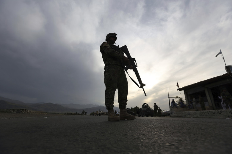 FILE – In this Saturday, April 4, 2020 file photo, an Afghan National Army soldier stands guard at a checkpoint to enforce a curfew for the the fight against the coronavirus, on the Jalalabad-Kabul highway, in the Laghman province, east of Kabul, Afghanistan. (AP Photo/Rahmat Gul, File)