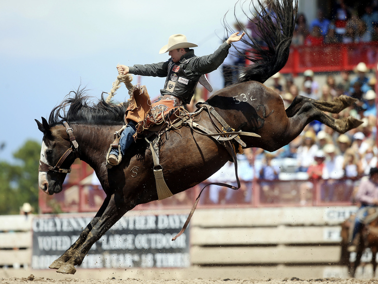 FILE – In this July 29, 2018, file photo, Brody Cress, of Hillsdale, Wyo. competes in the saddle bronc event during Championship Sunday of the 122nd annual Cheyenne Frontier Days Rodeo at Frontier Park Arena in Cheyenne, Wyo. When Augusta comes up, one instantly thinks of the Masters. If Omaha is mentioned, it's often in the same breath with the College World Series.  For those cities and others like them _ from Williamsport to Oklahoma City to Cheyenne _  the shutdown caused by the coronavirus pandemic is an especially wrenching blow. (Blaine McCartney/The Wyoming Tribune Eagle via AP, File)