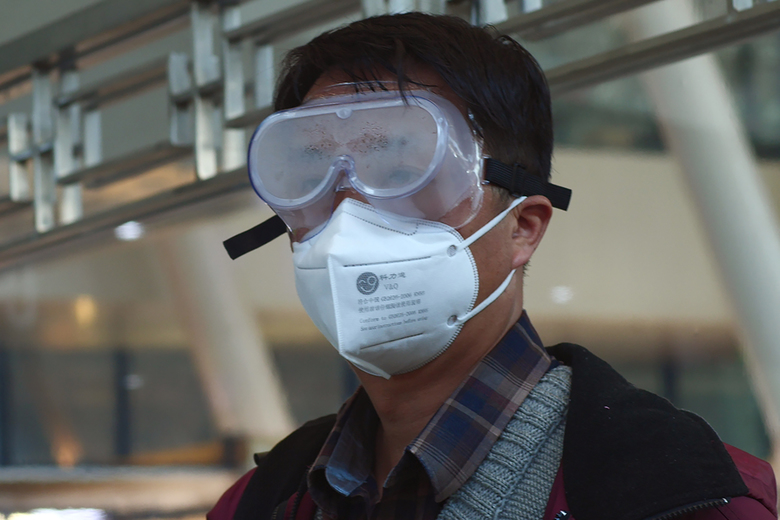 FILE – In this April 15, 2020 photo, a traveler stares out of a fogged mask while waiting for a train to Beijing from the train station in Wuhan in central China's Hubei province. Getting into Wuhan was the easy part as new infections had fallen to almost zero and travel restrictions were relaxed. As a 76-day lockdown neared its end, journalists were allowed to return to the Chinese city where the coronavirus pandemic originated. But getting out was proving harder. The bureaucracy had yet to finalize how people would safely organize their return and three official documents were needed: A green health code, home neighborhood approval and a recent nucleic acid test. (AP Photo/Sam McNeil, File)
