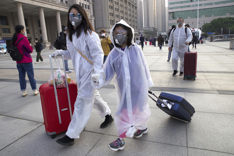 Passengers wearing face masks and rain coats to protect against the spread of new coronavirus walk outside of Hankou train station after of the resumption of train services in Wuhan in central China's Hubei Province, Wednesday, April 8, 2020. After 11 weeks of lockdown, the first train departed Wednesday morning from a re-opened Wuhan, the origin point for the coronavirus pandemic, as residents once again were allowed to travel in and out of the sprawling central Chinese city. (AP Photo/Ng Han Guan)