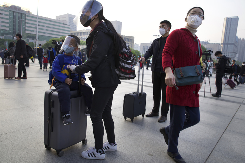 Passengers wearing face masks and face shields to protect against the spread of coronavirus gather outside of Hankou train station after of the resumption of train services in Wuhan in central China's Hubei Province, Wednesday, April 8, 2020. After 11 weeks of lockdown, the first train departed Wednesday morning from a re-opened Wuhan, the origin point for the coronavirus pandemic, as residents once again were allowed to travel in and out of the sprawling central Chinese city. (AP Photo/Ng Han Guan)