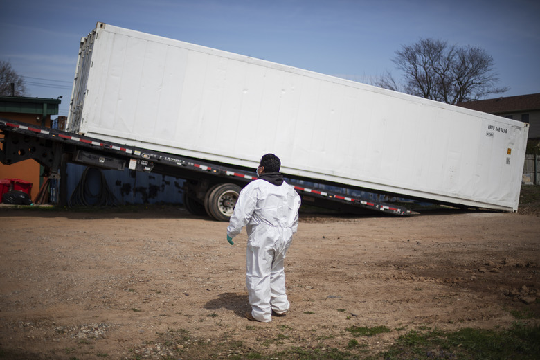 Gravedigger Thomas Cortez watches as a refrigerated trailer is delivered to keep pace with a surge of bodies arriving for burials, mostly those who died from coronavirus, at Hebrew Free Burial Association's cemetery in the Staten Island borough of New York, Tuesday, April 7, 2020. The organization stocked up on caskets before the coronavirus unleashed its worst, just as they did with protective gear for workers, garments for the dead and other supplies. They think they have enough. Then again, they thought the mortuary cooler they ordered a month ago to fit an extra four bodies would be enough extra space. Now they have a refrigerated trailer big enough to hold 20. (AP Photo/David Goldman)